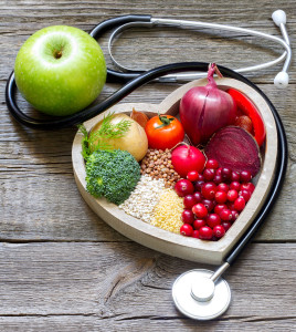 Healthy food in heart with stethoscope and green apple on vintage boards